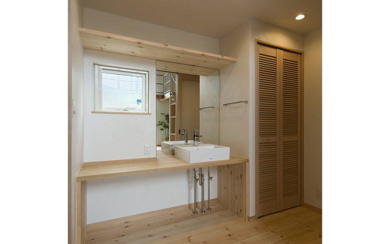 造作の洗面台とご主人の仕事着用クローゼット。毎日の動線をスムーズにすることにより、ストレスフリーに生活することが可能に。